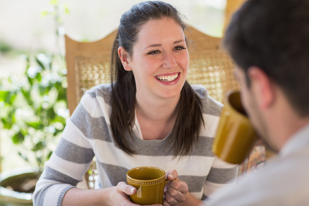 Couple having cup of coffee on patio