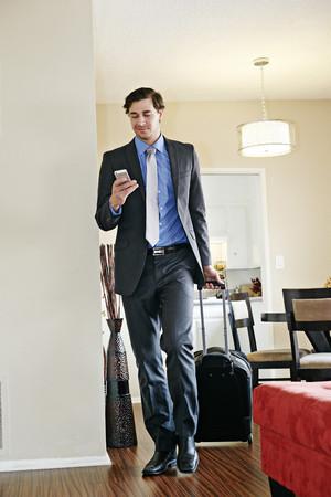 Caucasian businessman wheeling luggage