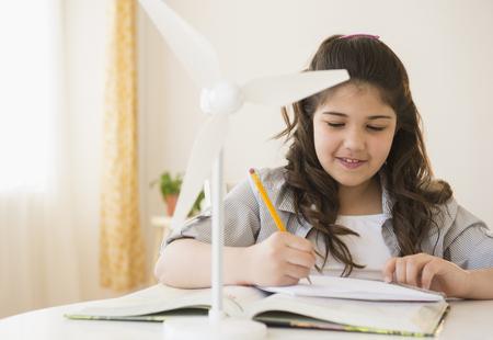 Hispanic girl with model wind turbine doing homework