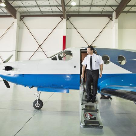 Caucasian pilot disembarking airplane in hangar