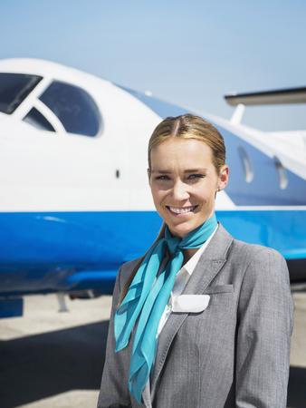 Caucasian flight attendant smiling on runway