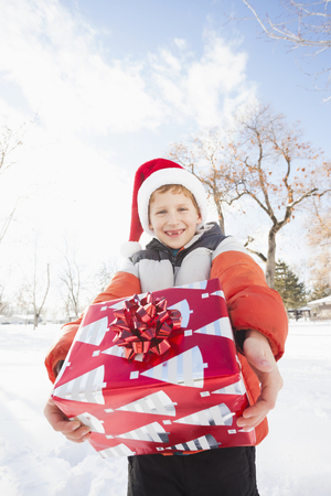 Caucasian boy in Santa hat holding Christmas present Stock Photo