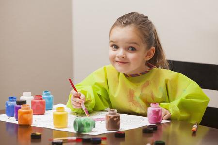 Kaukasisches Mädchen malt am Tisch
