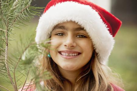 Mixed race girl smiling in Santa hat
