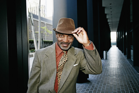 Black businessman tipping his hat Stock Photo