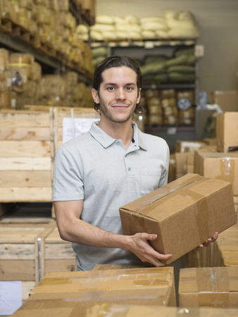 Mixed race worker stacking boxes in textile factory