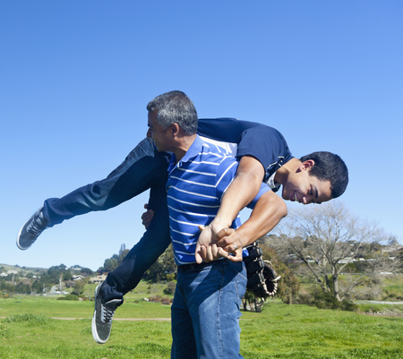 Hispanic father and son playing in park Stock Photo