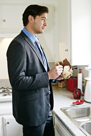 Caucasian businessman eating take out food Stock Photo