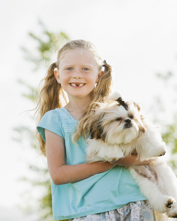 Caucasian girl holding dog outdoors