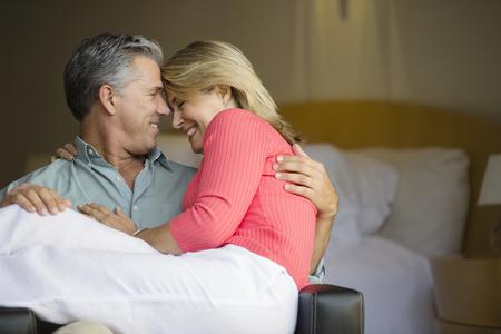 Caucasian couple hugging in armchair