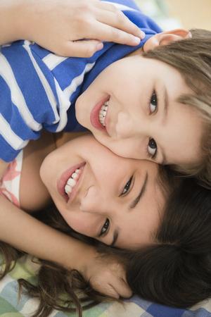 Hispanic children hugging on bed