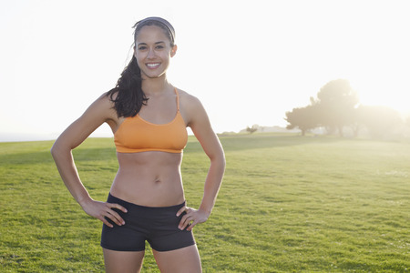 Hispanic woman smiling in field Stock Photo