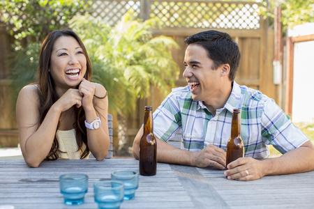 Couple having beers in backyard Stock Photo - 107917173