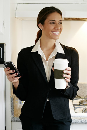 Mixed race businesswoman using cell phone in kitchen