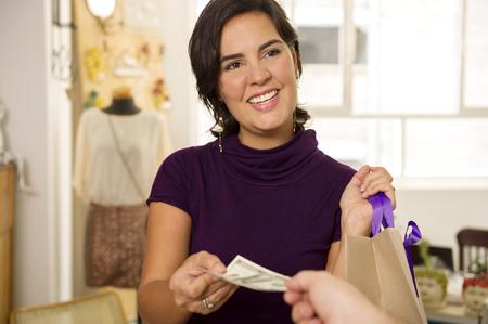 Hispanic woman shopping with cash Stock Photo
