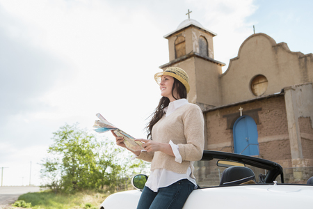 Caucasian woman reading map by church Stock Photo