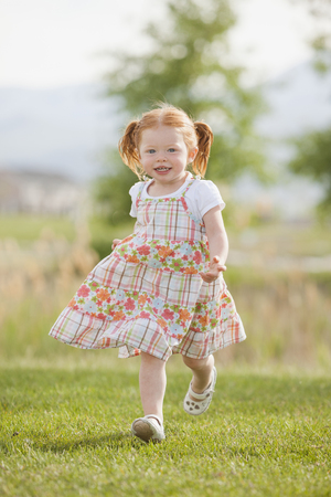 Caucasian girl running in grass