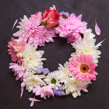 Un arrangement floral composé de fleurs roses et blanches, posé sur une ardoise fond rustique