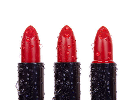 crimson colour: A close up of lipsticks with water droplets, isolated on a white background Stock Photo