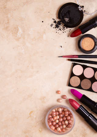cosmetics products: A selection of make up and cosmetic products arranged on a marble counter top background to form a page border