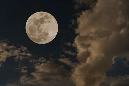 Full moon over clouds on the sky.