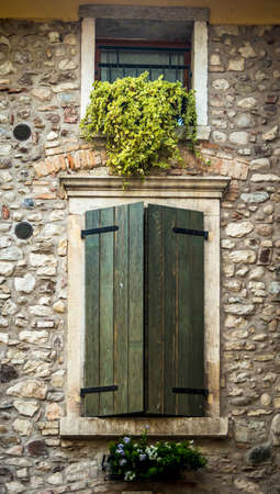 Window behind the green wooden shutters in Tuscany, Italy