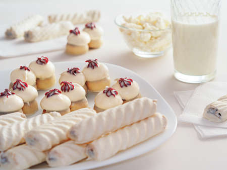 Tasty cookies and cakes lie on a white dish and napkins. Milk and cottage cheese are on the table. Dairy products and sweets. Food for sweets and milk lovers
