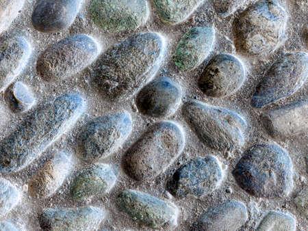 Una solida pavimentazione pavimentata con pietra tonda colorata. Fondo di pietra della pavimentazione del ciottolo Archivio Fotografico