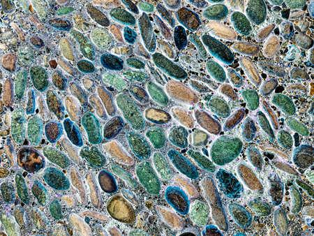 The road is paved with multi-colored cobblestones. Mosaic color background of cobblestone pavement Archivio Fotografico