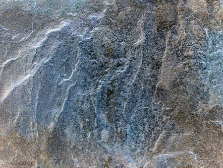 Silvery uneven structure of solid old stone. Natural stone background