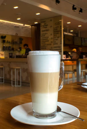 A glass of coffee is in the cafe on the table. Milk foam rose above the glass. Look inside the cafe