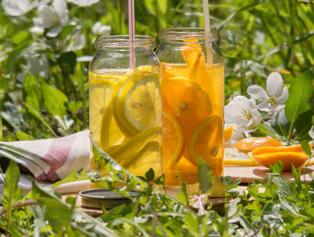 Refreshing drinks of lemon and orange on a hot summer day. Jars of lemonade stand in a clearing in the grass. Weekend for two