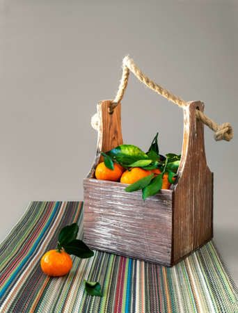 A small box with handles filled with tangerines. On tangerines leaves. A box is standing on a colorful napkin. Bright fruit background.