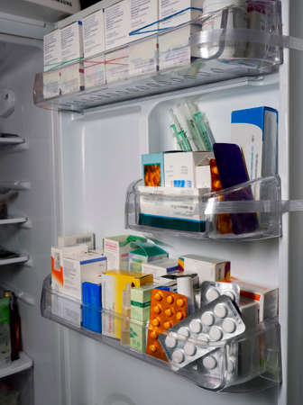 Background with medical drugs. On the shelves of the refrigerator door are packages of medicines, blisters with pills and syringes for injections.