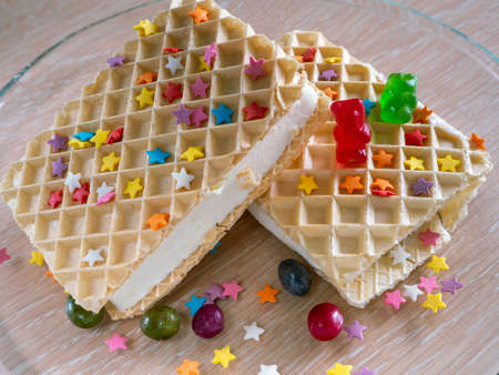 Ice cream briquettes in waffles close-up. Multi-colored stars are scattered on waffles and a plate. Dragees lie next to ice cream. Two marmalade bears lie on the waffle.