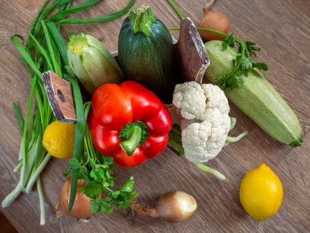 Rustic background with vegetables. Zucchini, bell pepper, and cauliflower are placed in a box with handles. Around the box are also vegetables.
