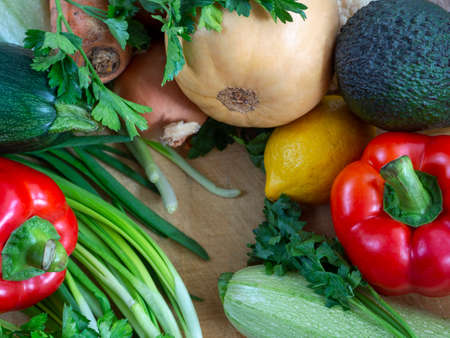 Fresh crop of vegetables laid out on a wooden table. Zucchini, pumpkin, bell peppers, herbs, lemons and avocados make up the colorful background.