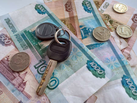 The key with the keychain lies on Russian money. Banknotes of one thousand, five hundred and one hundred rubles are visible, as well as small coins. Background with Russian currency and a key. Фото со стока