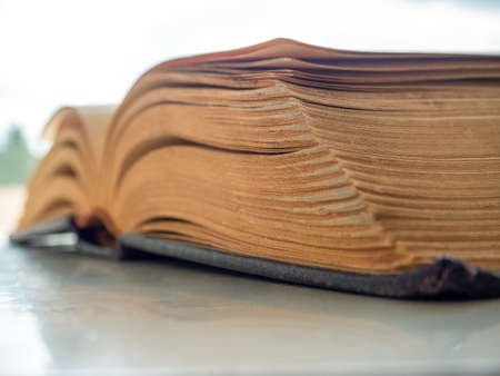 A thick antique book is open. Close-up. Selective focus. Background for libraries, education, science.