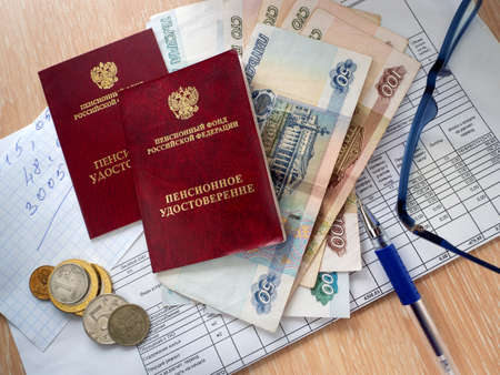 On the table are two pension certificates, paper and metal rubles, a receipt for utility bills, notes with calculations, a pen and glasses. Payment of utility bills by pensioners.