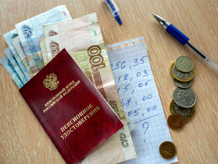 Pension certificate and Russian money on the table. Under them is a piece of paper with a budget estimate. Nearby coins and pen. Banque d'images