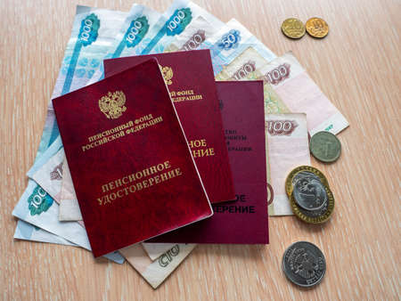 Three pension certificates lie on Russian money. Near metal ruble coins. Receiving and distribution of pensions.