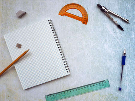 Background with a clean notebook and stationery. On the left is a notebook. A protractor, compass, pen, ruler and eraser are positioned around the edges of the background. Blank space on background. Stok Fotoğraf