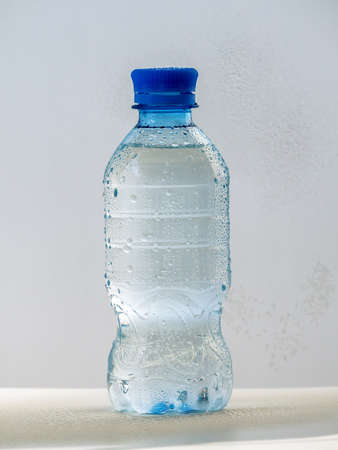 Plastic bottle with clean cold water on a light background. The bottle is closed with a lid. Water drops are visible on the bottle.