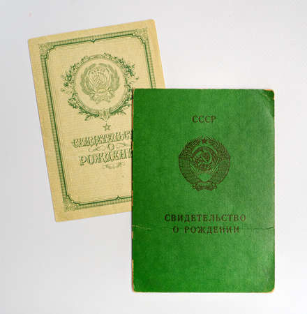 Two old-style birth certificates of a child obtained in the USSR. The certificates were registered at different times and differ in design. Papers isolated on white background.