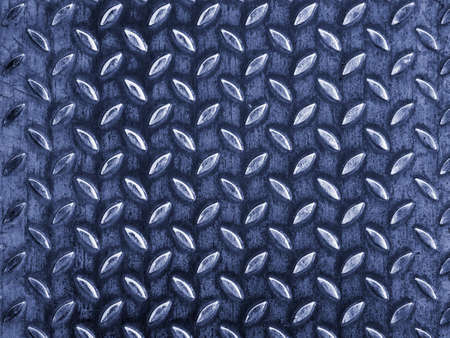 Metal surface are embossed with shapes that look like leaves. The leaves are arranged in lines and perpendicular to each other. A uniform pattern is formed from the figures.