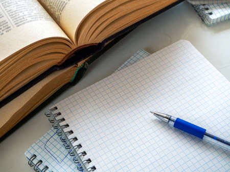 Two open books are on top of each other. There is a pen on a blank sheet of notebook. Empty space. Background for libraries, education, scientific work, university, school.