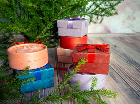 Holiday gift boxes are stacked on top of each other under spruce branches on the wooden floor. Bright Christmas background with gifts and fir tree.