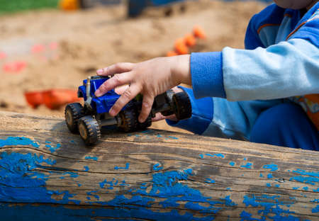 A child's hand holds a toy car and rolls it on a log. The child plays in the sandbox. Colorful background.