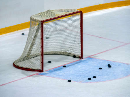 Hockey gates on ice close-up. Several pucks are visible near the goal and behind the net. The pucks remained on the ice after training.